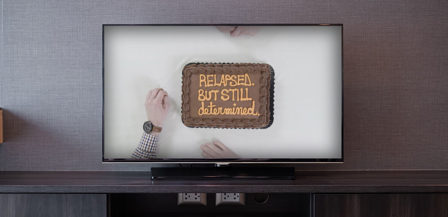 "TV shows cake with writing saying ""Relapsed but still determined"""