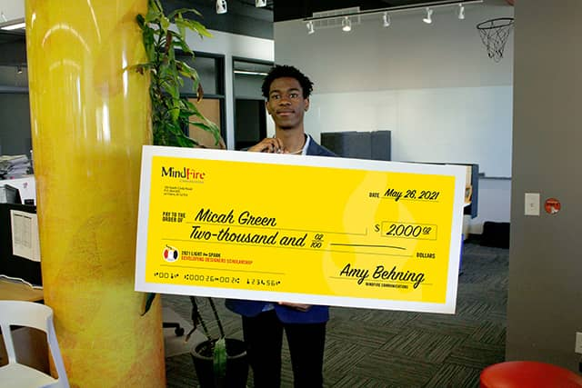 Micah Green holding a scholarship check