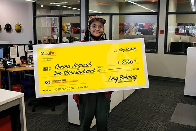 Omina Jagusah holding a scholarship check