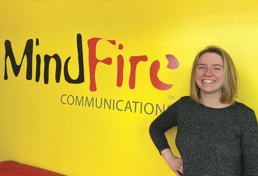 Creative Arsonist Caroline Schweitzer stands in front of MindFire sign in office lobby