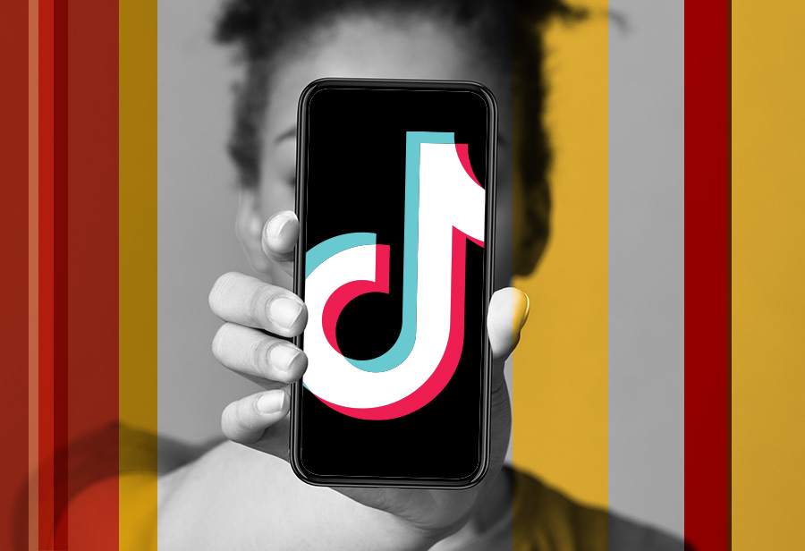 Person holds phone with TikTok logo in front of face